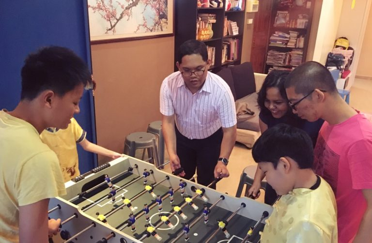 Mr Banderlipe (centre) playing table soccer with Ms Sia's sons and other guests. Image Source: Sia Yan Dih
